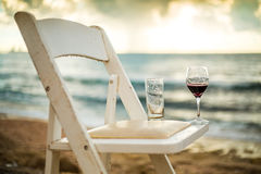 White chair with wineglass on a beach Stock Photography