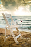 White chair with wineglass on a beach Stock Photo