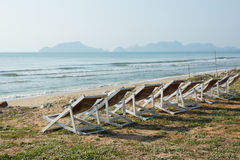 Chairs. White chairs on the beach, the sea and the mountains stock photos