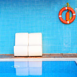 White chairs on blue background with an orange life buoy near swimming pool Royalty Free Stock Photo