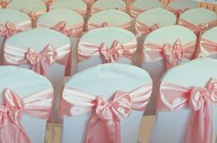 White chairs decorated with bows for party ,meetings and ceremonies. White chairs decorated with pink bows for party ,meetings and ceremonies stock images