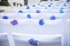Chairs decorated with flowers at a wedding ceremony. Stock Photos