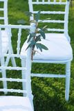 White Chairs Decorated with Ruscus Leaves at the Outdoor Wedding Ceremony Green Grass Background Party Celebrate Wedding Event stock photo