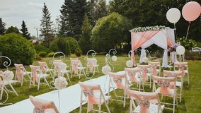 Wedding arch and white chairs in the open air stock video video of white chairs with a decorative light fabric in the open air at the wedding wedding junglespirit Image collections