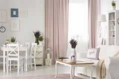 White chairs at dining table near posters in flat interior with pink drapes and settee. Real photo. Concept stock images