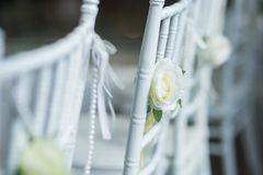 White chairs with flowers for a wedding ceremony. White chairs with flowers decoration for a wedding ceremony royalty free stock photo