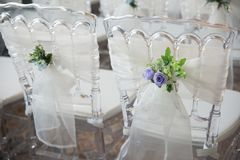 White chairs with flowers for a wedding ceremony. White chairs with flowers decoration for a wedding ceremony Stock Photo