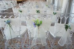 White chairs with flowers for a wedding ceremony. White chairs with flowers decoration for a wedding ceremony royalty free stock photos