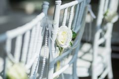 White chairs with flowers for a wedding ceremony. White chairs with flowers decoration for a wedding ceremony Royalty Free Stock Image