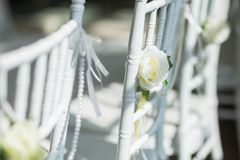 White chairs with flowers for a wedding ceremony. Stock Photo