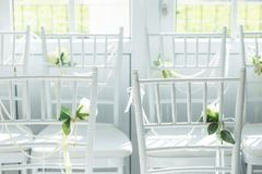 White chairs with flowers for a wedding ceremony. White chairs with flowers decoration for a wedding ceremony stock photos