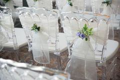 White chairs with flowers for a wedding ceremony. White chairs with flowers decoration for a wedding ceremony Royalty Free Stock Photography