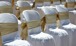 White chairs with gold ribbon at a beach wedding. Multiple chairs set up on a sandy beach ready for a beach wedding ceremony Stock Photos