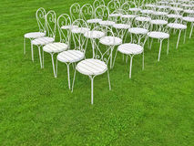 White chairs in the green field Royalty Free Stock Photo