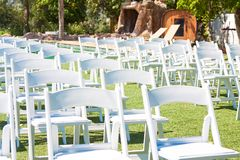 White chairs on green grass. Preparing for the outdoor wedding ceremony. royalty free stock photo