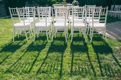 White chairs on a green grass. White chairs at the wedding are on the green grass on a sunny day, and the long shadow of them Stock Photography