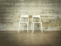 White chairs near concrete wall Royalty Free Stock Images