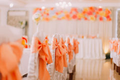 White chairs with orange ribbon decoration at a luxury wedding hall Royalty Free Stock Photo