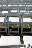 White chairs for outdoor event. Organized rows of white, wooden chairs neatly arranged for an outdoor ceremony or event, like a wedding, concert, commencement Stock Image
