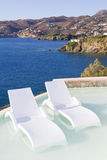 White chairs in pool with sea view Stock Images
