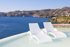 White chairs in pool with sea view in Greece Stock Photography