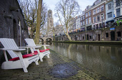 White chairs river front just next to the water. These buildings and areas are very cozy on a narrow streets. Vibrant colors of the windows and  walls. Lights in Royalty Free Stock Images