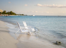 White Chairs on the Shore of a Tropical Beach Royalty Free Stock Photography