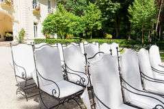 White chairs stand in the rows before wedding altar Stock Photos