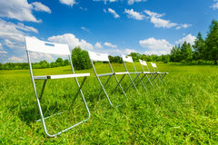 White chairs standing in a row on green grass Royalty Free Stock Photography