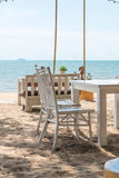 White chairs and table on beach with a view of blue ocean and cl Stock Photos