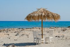 White chairs and table with view of tropical turquoise ocean under a straw umbrella Stock Images