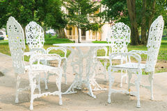 White chairs and table in green park Royalty Free Stock Photo