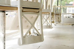 White chairs on tables upside down on street cafe summer terrace. Royalty Free Stock Photos