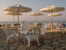 White chairs and umbrellas on a hotel terrace Royalty Free Stock Photo