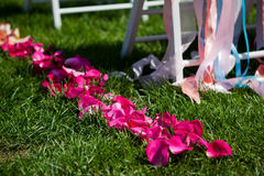 White chairs for a wedding ceremony. Rose petals adorn the path to the wedding arch Royalty Free Stock Photo