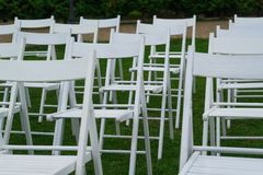 White chairs on wedding venue with green grass on background. Wedding Set Up. Wedding setting. Wedding venue. White chairs on green grass with night lights Stock Images