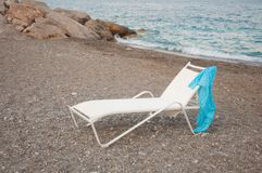 White chaise-longue with blue fabric pareo on sea beach. White chaise-longue with blue fabric pareo on the pebble sea beach stock images