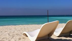 White chaise longue on sandy beach and splashing sea waves. Two beach chair on summer beach on background turquoise waves in sea water stock video