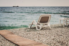 White chaise lounge on a beach of pebbles Royalty Free Stock Images