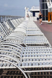 White Chaise Lounges on Deck. A ships deck with a row of chaise lounges and a woman out of focus running in background stock photos