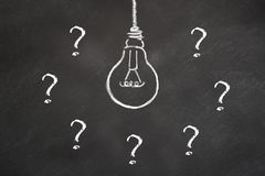 Chalk bulb idea with question marks on a blackboard royalty free illustration