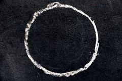 White chalk drawing as circle shape on black board. Background stock image
