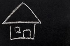 White chalk drawing as house shape on black board. Background Concept of dream home, happy family royalty free stock images