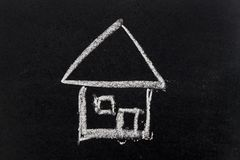 White chalk drawing as house shape on black board. Background Concept of dream home, happy family Royalty Free Stock Photography