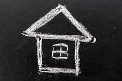 White chalk drawing as house shape on black board. Background Concept of dream home, happy family Stock Image