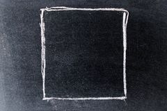 White chalk drawing in blank square shape on black board. Background royalty free stock photo