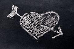 White chalk drawing in heart with arrow shape on black board. Background use for decoration in valentine, love, couple or engagement concept royalty free illustration