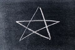 White chalk drawing in star shape on black board. Background royalty free stock photos