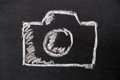 White chalk hand drawing as camera icon on black board. Background Stock Images