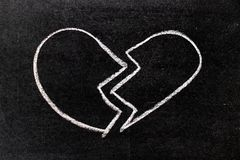 White chalk hand drawing in broken heart shape on blackboard royalty free stock photography